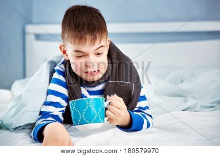 Ill boy lying in bed. sad child with fever and cup of tea