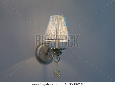 Old style switched on lamp mounted on blue wall with lampshade