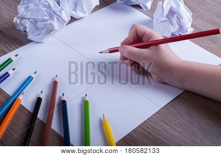Colored pencils on white paper back to school concept - Child's hand preparing to write on a white sheet of paper with pencils and drafts