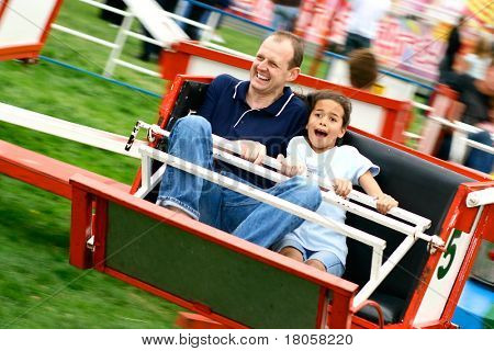 Father and daughter enjoying the fast octopus ride at the amusement fair in the park.