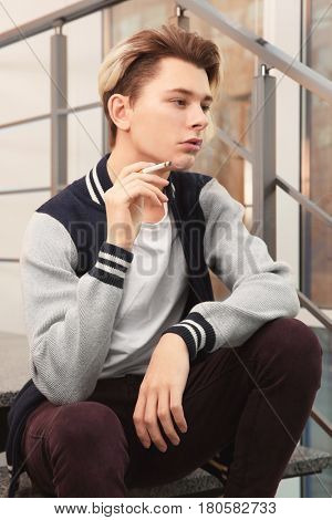Teenage boy sitting on stairs and smoking