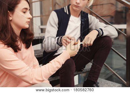 Teenage couple sitting on stairs and smoking