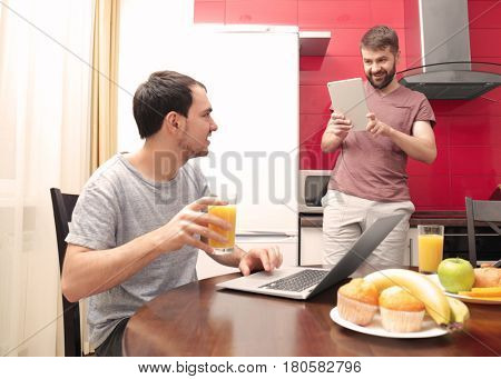 Gay couple using laptop and tablet while having breakfast in kitchen