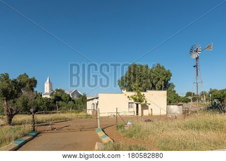PHILIPPOLIS SOUTH AFRICA - MARCH 21 2017: A street scene with a house windmill and the Dutch Reformed Church in Philippolis the oldest town in the Free State Province