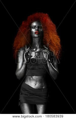 Beautiful young woman with amazing body-art as lion on dark background. Zodiac signs concept