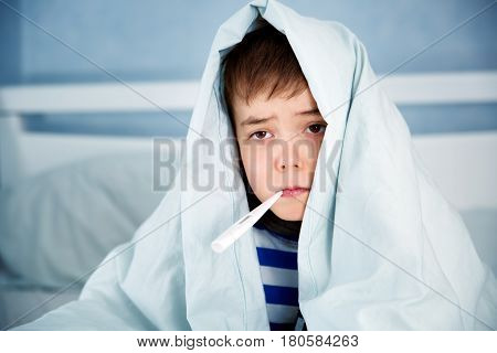 Ill boy lying in bed. sad child with fever wrapped in a blanket