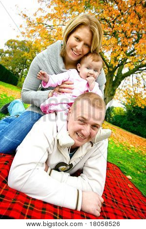 Young family with baby girl in an autumn park, having fun