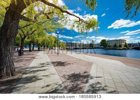 Park in Stockholm Sweden Scandinavia Europe. Trees and walking lanes with old town blue sky with clouds (gamla stan) in background.