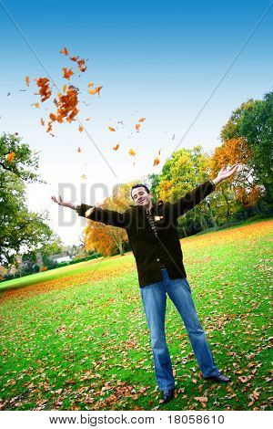Young man having fun throwing up piles of autumn leaves .
