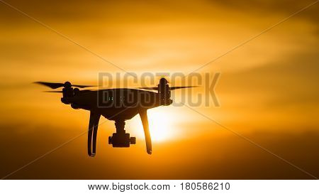 poster of drone quad copter with digital camera at sunset ready to fly for surveillance. close-up of Rotor drones. 4 blade propeller drone. silhouette drone on sunset. Drone Video Camera.