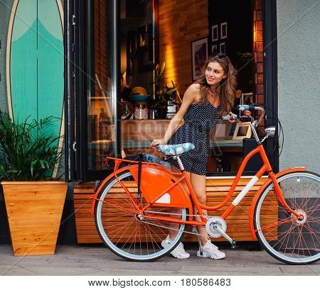 Cute girl in a summer dress stands with red vintage bicycle and looks around in search in a European city. Sunny summer. The girl in a good mood, she laughs. On background surf cafe. Outdoor. LA. California.