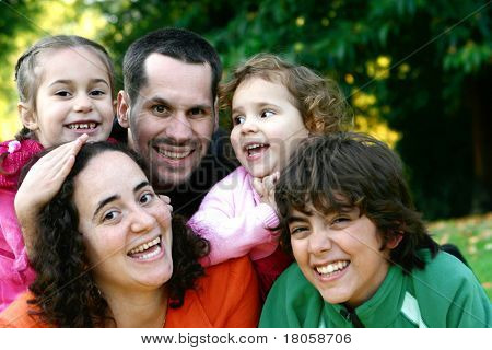 Beautiful young family having fun playing in the park.