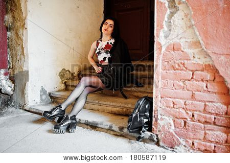 Young Goth Girl On Black Leather Skirt And Jacket With Backpack Posed On Stairs Of Old House.