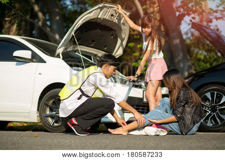 Asian insurance agent to quick attention in the spot of accident after both cars crashed occurrence with injured people in background
