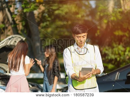 Insurance Concept;Front view of insurance agent writing on tablet while examining car