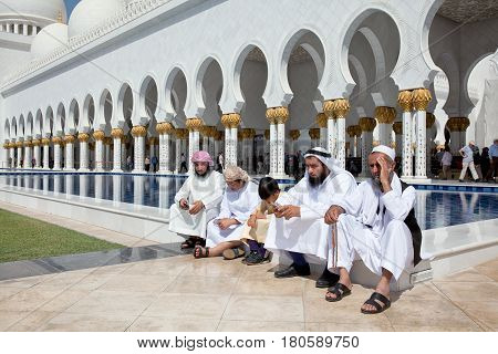 ABU DHABI UAE - March 18 2017: Arab men in front of the Sheikh Zayed Grand Mosque in Abu Dhabi United Arab Emirates. It iis the largest mosque in United Arab Emirates for more than 40000 prayers.arab men