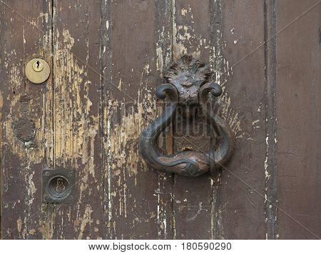 inactive iron doorknob on a shabby brown door with modern lock in Lisbon, Portugal