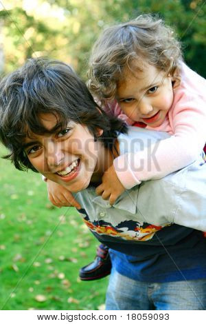 A young boy carrying his sister on his back as they play outdoor in the park