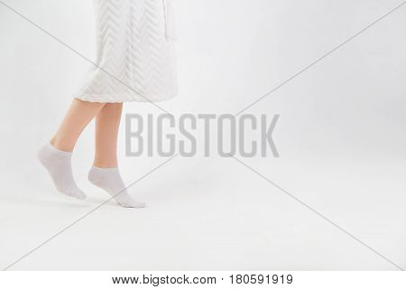 Feet of woman going on tiptoe at home.