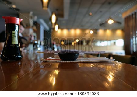 BEER SHEVA ISRAEL - APRIL 08 2017: Bottle with soy sauce and a rosette with chopsticks are on the counter of sushi bar