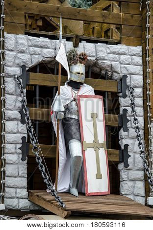 Knight Crusader with shield and spear guards the gates of the castle
