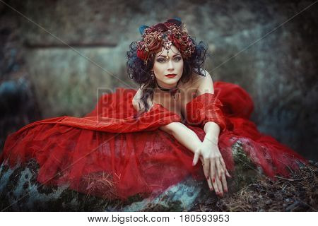 A fairy-tale image of a girl in a red dress in a forest with big stones