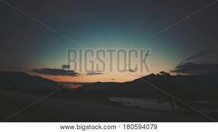 Scenery wide angle view of dirt road in foreground near Katun mountain river on late sunset with mountains village and hills in background pine tree and dark scenery teal summer sky Altai Russia