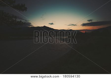 Scenery wide angle view of late sunset in district of mountain river Katun with mountains and hills in background and dark dramatic teal and orange summer sky Altai Russia