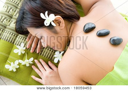 Young woman in hot stone therapy, resting on massage bed surrounded with white orchid.