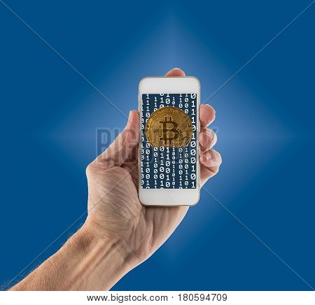 Gold bitcoins on blue background and emerging from app on smartphone to illustrate concept of blockchain for mobile money payments