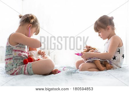 Girls sisters play doctor with dolls concept maternity joint game lifestyle