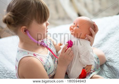 Kid girl playing with a doll playing doctor with a stethoscope taking care of a doll concept maternity lifestyle and childhood