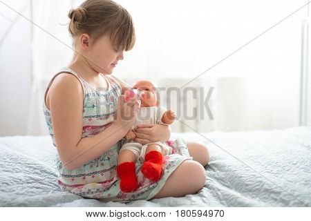 Kid girl playing with a doll feeding a doll from a bottle taking care of a doll concept maternity life style and childhood