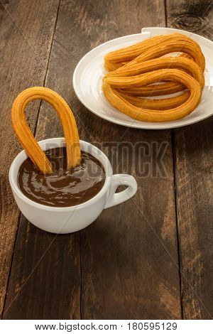 An overhead photo of a churro, traditional Spanish, and especially Madrid, dessert, particularly for Sunday breakfast, dipped into hot chocolate. With a place for text