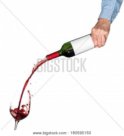 Red wine being poured directly from wine bottle with a blank label into a large goblet