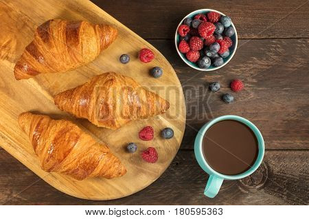 An overhead shot of crunchy French croissants with fresh raspberries and blueberries on a wooden cutting board, with a cup of chocolate and copy space