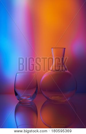 Still life with a glass and a decanter. Backlighting through multi-color filters