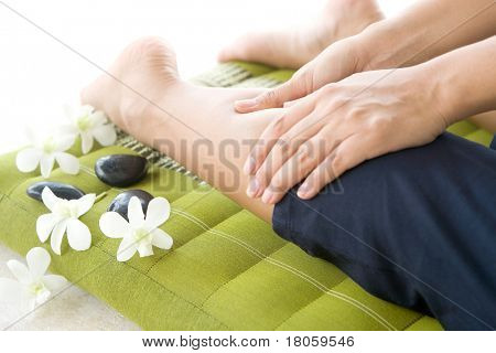 Masseur giving lady patient a leg massage .