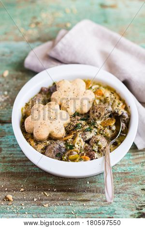 Baked champignons mushrooms, chicken liver with carrot, onion in cream sauce served with wheat cheese scones in a bowl, selective focus
