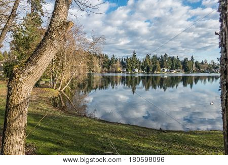 Homes trees and sky are reflected in the water of Mirror Lake in Federal Way Washington.