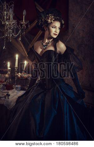 Girl in a black rococo dress in a dark cherry-colored interior