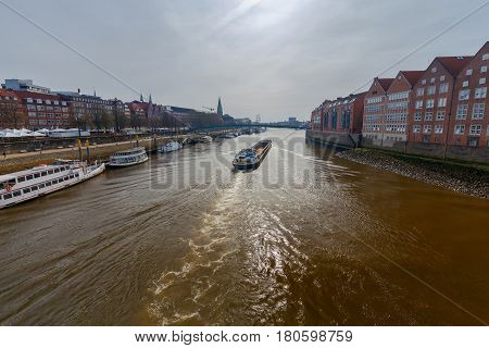 A self-propelled barge runs along the Weser River in the city of Bremen.