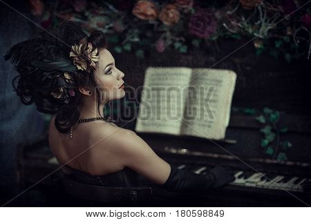Girl in a black dress with a piano in a dark room. Rococo