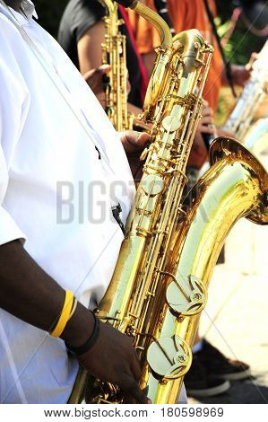 African american male playing a baritone sax in concert outside.