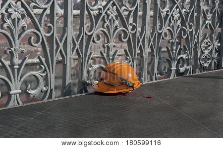 an orange construction helmet with earphones forgotten on the floor of observation deck in Lisbon, Portugal