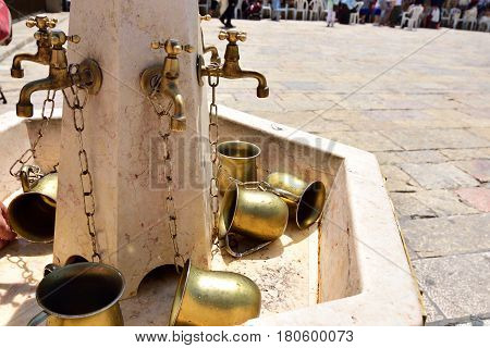 Water standpipe and copper pots for ritual ablution on square near Wailing Wall in Jerusalem.
