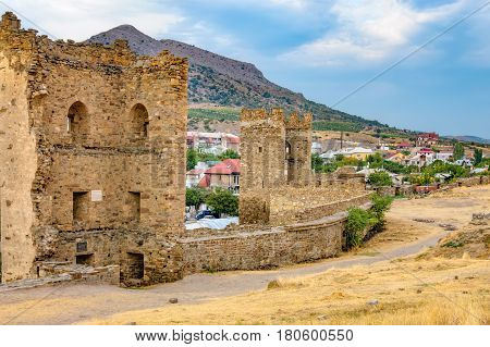 Walls of Genoese fortress in Sudak Crimea. Scenic views of rocky cliffs near ancient Genoese fortress and modern city in the background