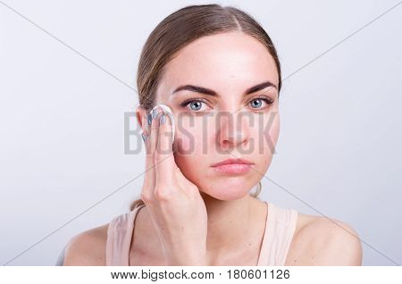 Beautiful Young Woman Cleansing Her Face With Cotton Sponge