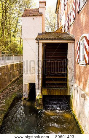 NeuoettingGermany-April 82017: A working water mill used for power generation turns next to a house
