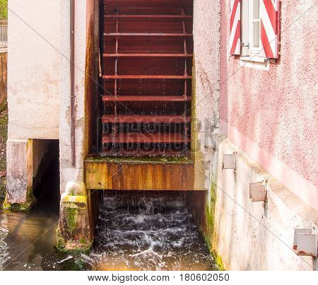Neuoetting,Germany-April 82017: A working water mill used for power generation turns next to a house